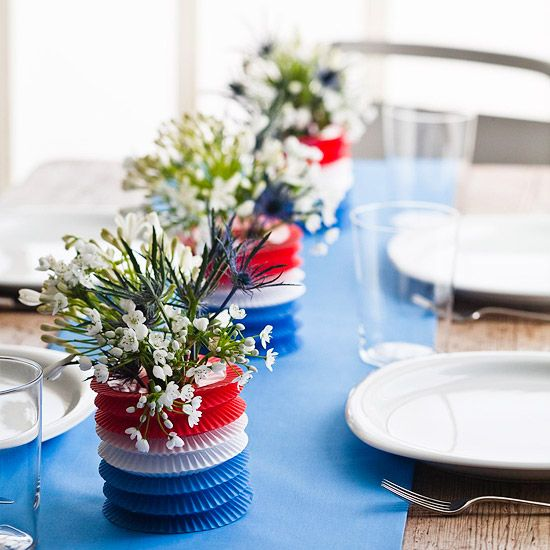 Red, white, and blue striped lanterns can become makeshift centerpieces for your table. Just slip each lantern over a clear glass and tuck a handful of white blooms inside. A solid blue runner across the table will make these decorations pop. (BHG.com)