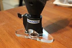 Dremel Router Base by Tuomas -- I wanted a tiny and accurate router base for making inlays. Used Dremel circle cutting guide, i had one spare and it has nice height adjustment, so it made things much easier. Ripped off.. Shortened these fingers a bit to get larger scale for the height adjustment. Made the base from acryl, polished it and shaped the original frame to get better view to workpiece. Piece of tape in the routing bit blows the dust away. It actually works. Final product has…