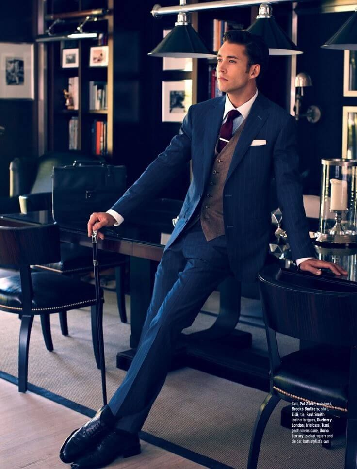 プンストライプのネイビースーツにツイードベストを合わせた着こなし。ボルドーのネクタイが印象的。