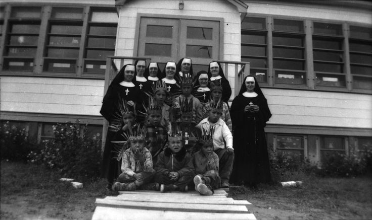 A Photo History of Residential Schools -Sisters of the Soeurs du Sacré-Coeur d'Ottawa and students on the steps of the school on the Pukatawagan Reserve in Manitoba in 1960.