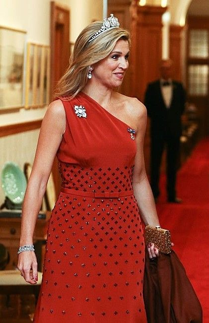 Queen Maxima of The Netherlands, stepping out flawless in the embellished one-shoulder gown by Dutch designer Claes Iversen. The couture design featured embellishments on the skirt and bodice, adding a touch of glamour to the deep red fabric. She accessorized with a gold clutch and diamond bracelet and wore the Queen Emma Diamond Tiara, during a state banquet at Government House in New Zealand.
