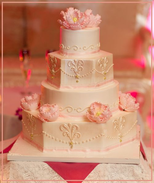 This beautiful 4-tier wedding cake is iced in ivory, with 2 of the tiers pearlized, and has a touch of blush pink ribbon on the bottom of each tier. Delicate swirls go around each of the tiers as well and beautiful pink peonies have been added on. To make the cake unique, 2 tiers of the cake were made in a hexagon shape, which gives this cake a different dimension.