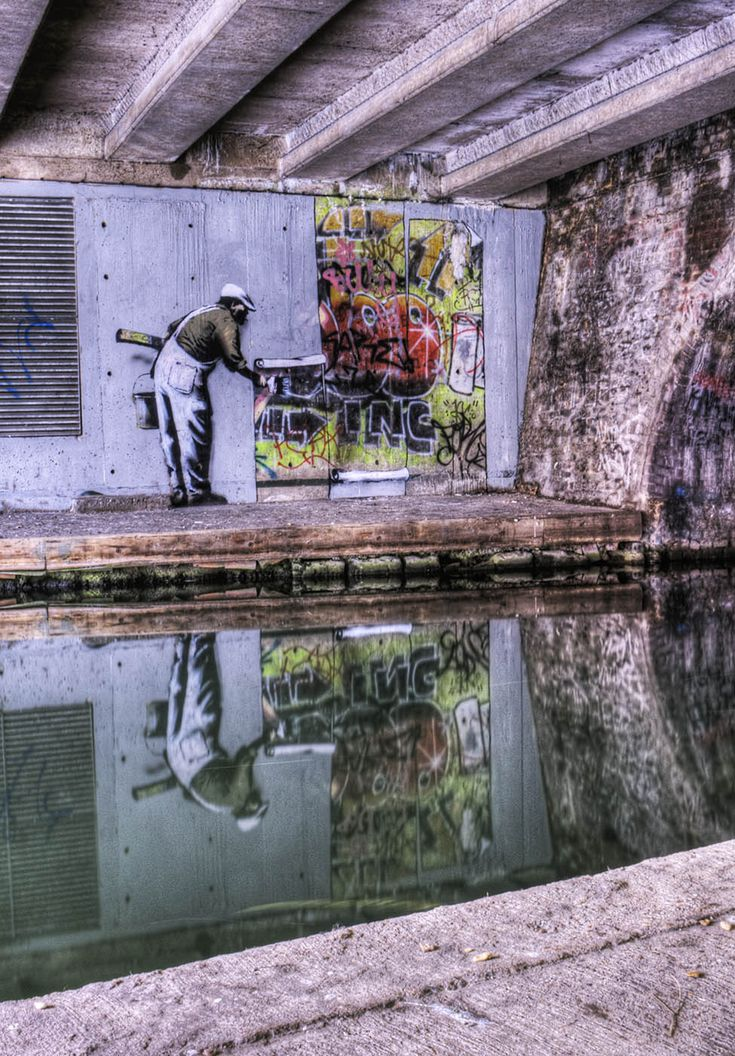 Stencil by Banksy (painter / paste-up piece) over historical Robbo graffiti in Camden by Regent's Canal