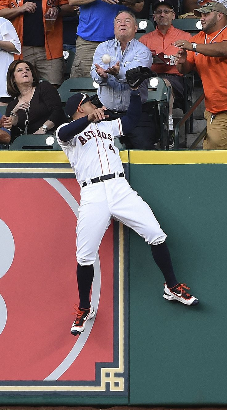 Houston Astros right fielder George Springer leaps in vain for a solo home run by Kansas City Royals' Mike Moustakas during the first inning of a baseball game Thursday, April 14, 2016, in Houston.