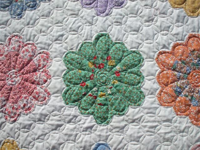 Curved quilting on hexagon's give rounded appearance to flowers -- Grandma's flower garden or hexagon quilt
