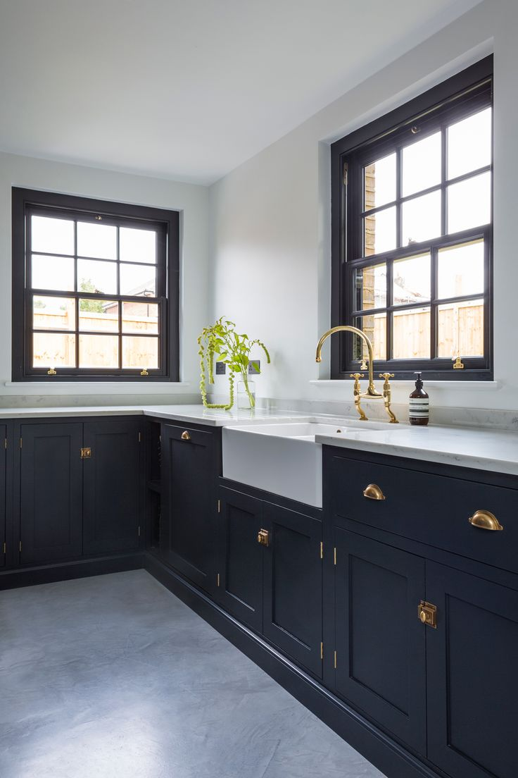 The stunning Kempshott Road deVOL Kitchen features polished concrete floors, beautiful brass hardware and a big farmhouse sink. Photo credit: Nathan Pask