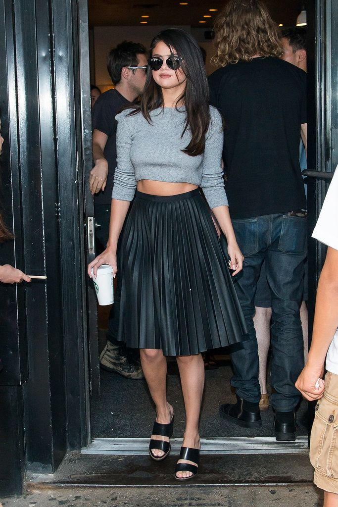 Selena Gomez wore a pleated skirt paired with a cropped sweater and sandals.