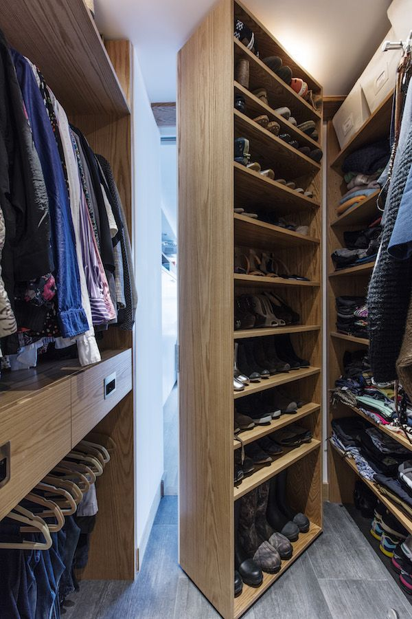 Using the door to the old closet, Kris custom built movable shelving units out of corresponding walnut wood for shoes and other sections for hanging clothes. These movable units lead to a separate bathroom entry to the back of the studio, where the living room sits.