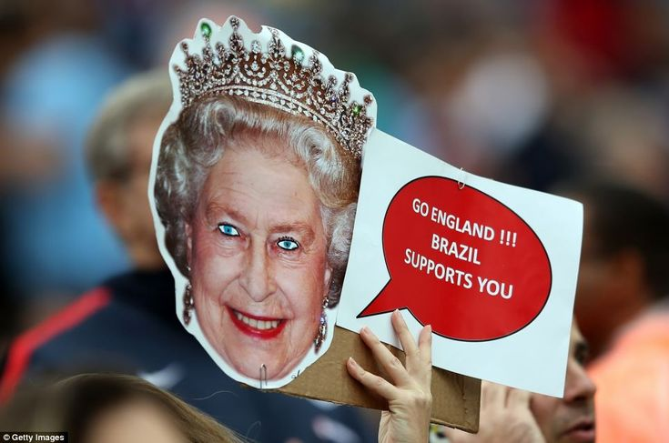God save the Queen! A fan holds a royal mask with the words 'Go England!!!'...