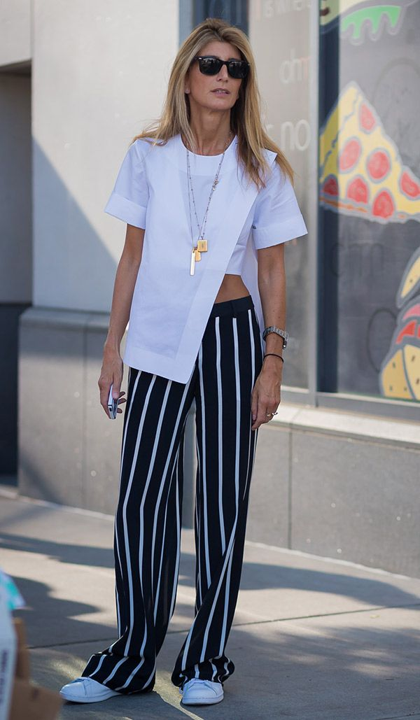 Street style look com blusa branca e calça listra.