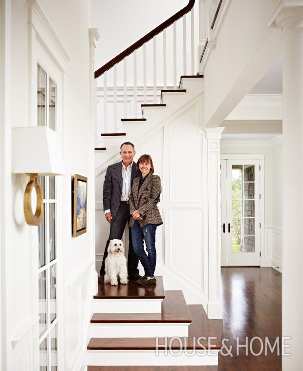 Homeowners Susan Sinclair-Brockelsby and Gerry Brockelsby with their cockapoo, Sam, in the crisp white panelled hallway of their Caledon weekend home. | Photographer: Angus Fergusson | Designer: Sarah Richardson and Natalie Hodgins