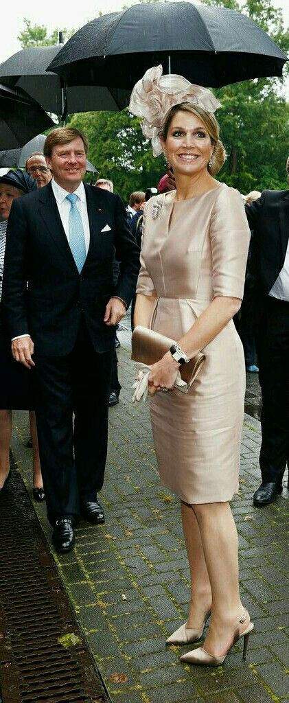 Maxima dont cares about the rain. Beauriful as always. Her husbant looks amused.
