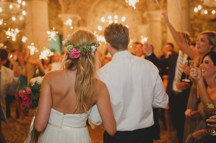 the bride wears her flower crown as she and her groom leave the reception under the dazzling glow of sparklers.