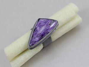 Przedstawiam Państwu piękny, oryginalny pierścionek wykonany od podstaw ręcznie ze srebra próby 925 i naturalnego czaroitu wielkości ok. 28x13 mm. Kamień jest cudownie wybarwiony. Gdy patrzy się na niego, ma się wrażenie, że jego wnętrze jest trójwymiarowe. Na powierzchni kamienia widoczne są naturalne rysy i spękania.Pierścień niejest odlewem, każdy srebrny element został ręcznie ze sobą zlutowany. Srebro zostało zoksydowane oraz przetarte do uzyskaniasatynowej, matowej struktury.…