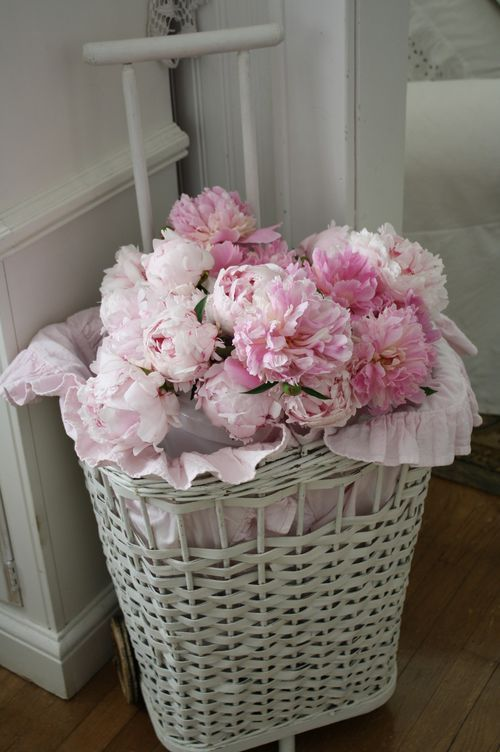 white wicker basket with the pink ribbon and beautiful flowers
