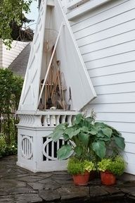 Obelisk for gardening tool storage and to conceal air conditioner. Beautiful!
