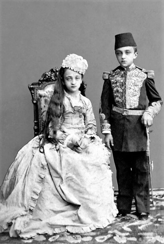 The Ottoman prince Abdülmecid and princess Nazime in ceremonial dresses.  Istanbul, ca. 1880.  Both are children of sultan Abdülhamid II.  The boy is the future last caliph of the Ottoman house.