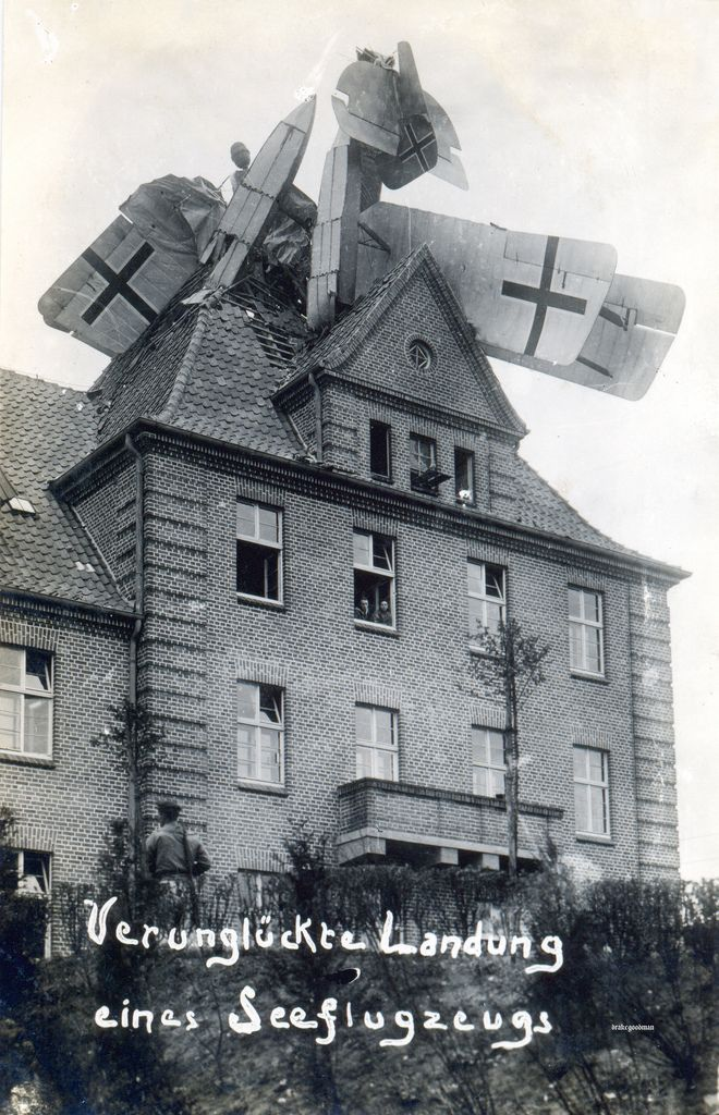 """A crashed Friedrichshafen FF.49 two-seat reconnaissance seaplane pokes out of the top of one of the taller buildings near its base in Germany (1918). You can just make out the """"lozenge camouflage"""" pattern on the aircraft's tail which was used from late 1916 until the end of the war. [660 × 1024]"""
