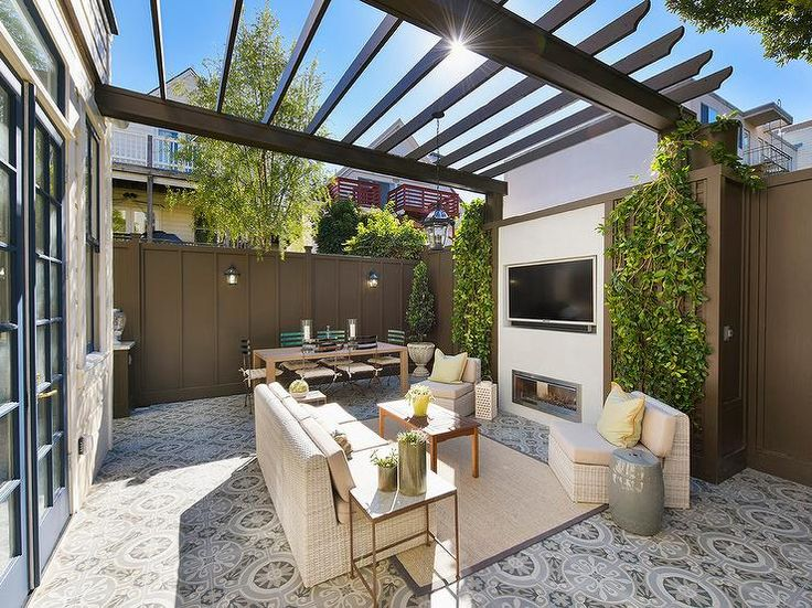 Beautifully appointed backyard features a stunning gray pergola fixed above eye-catching cement floor tiles complementing an ivory wicker sofa placed on a bound sisal rug facing a teak coffee table flanked by ivory wicker chairs warmed by a small fireplace fixed under an inset television.