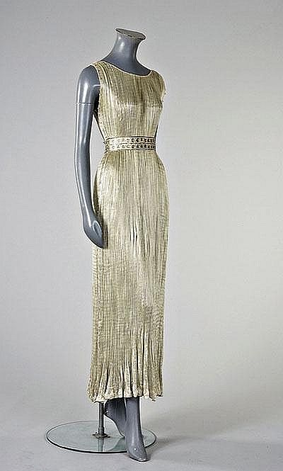 Mariano Fortuny dove-grey Delphos gown, circa 1930, printed with maker to the inner selvedge, the armholes and side seams edged in clear Murano glass beads, the satin belt stencilled with silver vines
