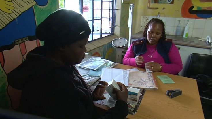 Image: An HIV positive woman, left, receives antiretroviral drugs at a clinic in Hammanskraal, South Africa.