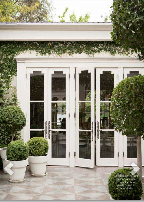 detailed French doors lead to a manicured terrace #architecture #frenchdoors