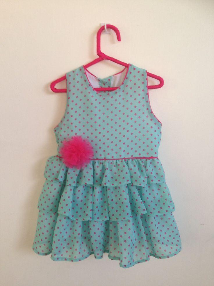 Vestidito con falda de vuelos en chifón turqueza con bolitas y detalles en fucsia. El prendedor de flor se puede usar en el cabello.  Talla 3 años.