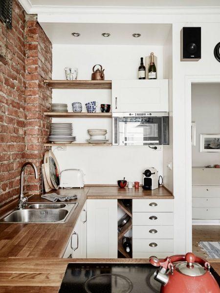 biała kuchnia skandynawska z drewnianymi blatami i półkami i ścianą z czerwonej cegły -…