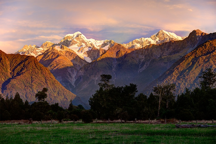 Sunset arrives on the West Coast of the South Island, painting Mt Tasman and Mt Cook in wonderful hues.