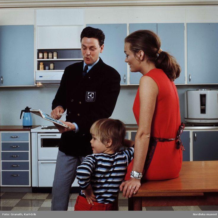 DigitaltMuseum - Representant från Electrolux hemtjänst samtalar med kvinna i ett kök och visar produktkatalog
