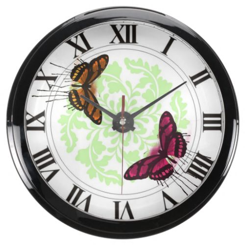A fabulous clock with beautiful pink and orange butterflies and a floral pattern with roman numeral numbers, very stylish. #butterflies #butterfly #pink-butterfly #orange-butterfly #roman-numerals #roman-numerals-clock #butterflies-clock #pink #orange #green
