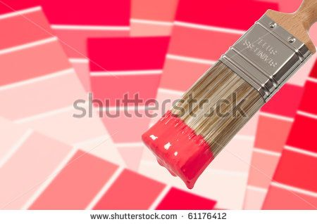 Paint brush loaded with red paint with colour swatches below