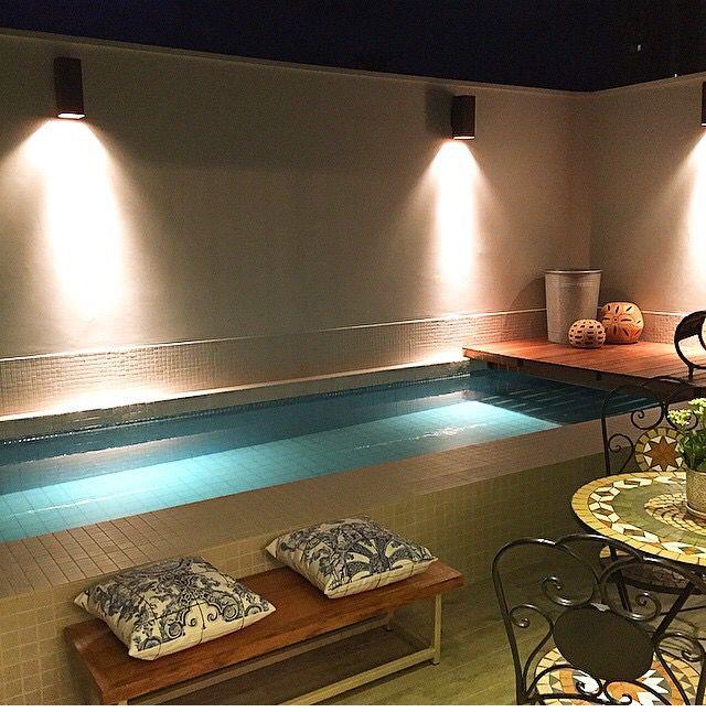 Aqui a iluminação traz um visual a ser desfrutado pela beleza do efeito que realiza no muro muito limpo de informação! A decoração e ambientação fica por conta do deck de madeira sobre a água ... Assim a piscina ganha mais espaço pra sol !