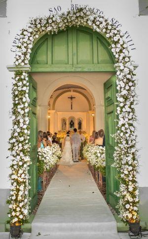 Casamento de Gabriela Meira e Borja Rodriguez na capela da Praia dos Coqueirais, em Pernambuco, com uma vista maravilhosa nos arredores e o charme do arco de flores brancas.