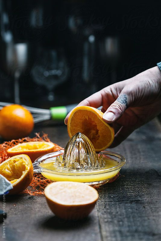 Woman's hand squeezing orange's in a glass juicer. by Darren Muir. Available to licence on stocksy. DARRENMUIR20 for 20% discount on checkout. #discount #code #stocksy #stock #photography #Seville #orange #curd #dark