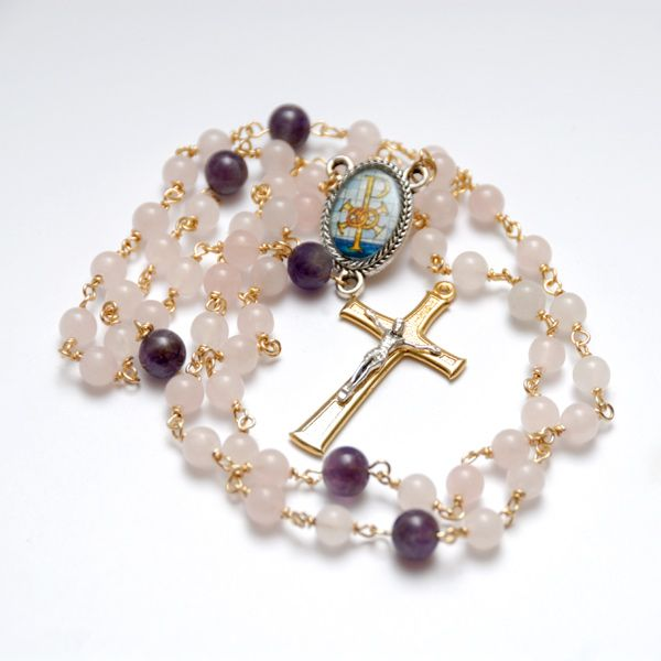 Pósadh Gemstone Wedding Rosary - A beautiful heirloom rosary to give on the occasion of an engagement, marriage or anniversary. Crafted with delicate soft pink rose quartz and exquisite amethyst semi precious gemstones. The center medal is antique silver plated with a glorious colour depiction to symbolise unity or marriage.