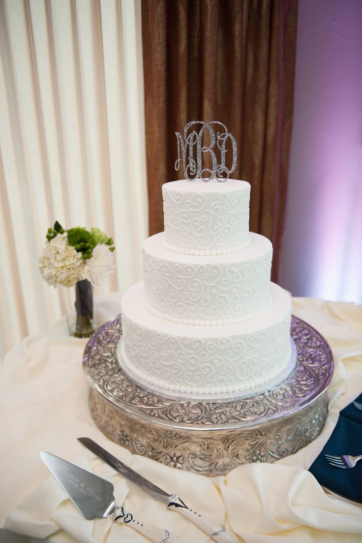 White Swirling Wedding Cake With Monogram Cake Topper