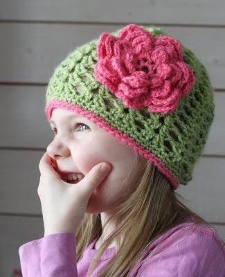 En glad vårgrön mössa med en stor rosa blomma