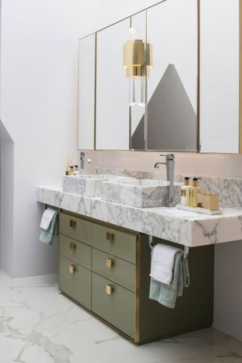 Marble bathroom with green and brass cabinetry