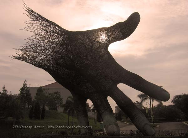 """This steel mass """"piece of hand"""" sculpture is located at the gate of Setraduta, an upper class housing complex in the north of Bandung. It is designed and made by Nyoman Nuarta, one of the most prominent and prolific Indonesian sculpturers today."""