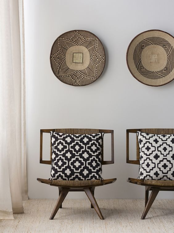 Dark wood chairs upholstered with ethnic woven fabrics and matching pottery on the wall