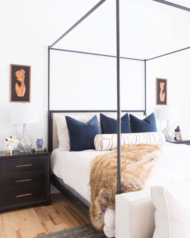 Modern eclectic master bedroom with an iron canopy bed, vintage art, a faux fur throw and white bedding with navy blue pillows - Bedroom Ideas & Decor