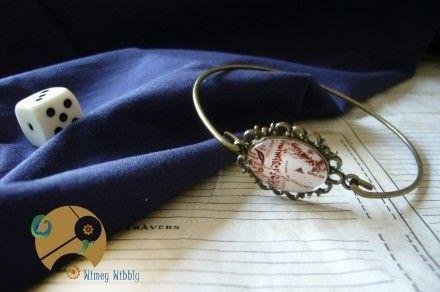 Joli bracelet à cabochon représentant la zone entre le Mordor et le Gondor sur la carte de la Terre du Milieu issue du roman Le Seigneur des Anneaux de J.R.R Tolkien. Un bijou tout en élégance rétro avec une touche d'originalité médiévale-fantastique.