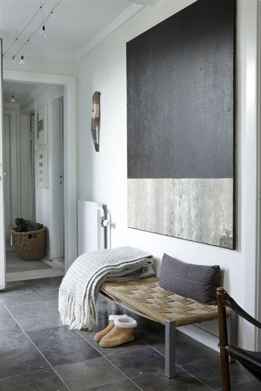 Urban spirit in this minimal hallway. Neutral colours are a winning combination supporting modern art and rattan bench.