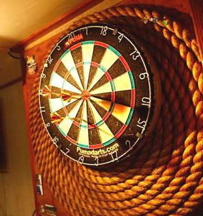Clever use of coiled rope as a dartboard surround, cushions the impact of darts if you miss the dartboard!