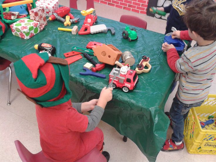 "Set up a Santa's Workshop for a preschool Christmas activity. Include elf hats, toys to be ""built."" tools and paint brushes, gift boxes and bags."