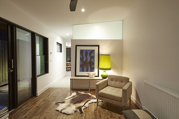 Night time image of the living room to the bathroom space