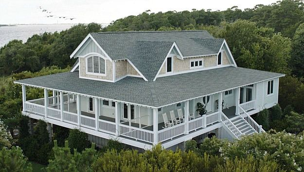 This hamptons style home looks like a huge tree house above those trees like that. My favourite kind of house!