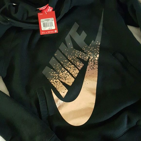 BNWT Nike pullover hoodie Black pullover hoodie with Nike logo in metallic rose gold foil & dark gray almost black color. The hood is made to look like a cowl neck in the front but you are still able to wear the hood over your head. Has kangaroo pockets. It's a warm cotton sweater. Feel free to send offers! Brand new with tags Nike Tops Sweatshirts & Hoodies