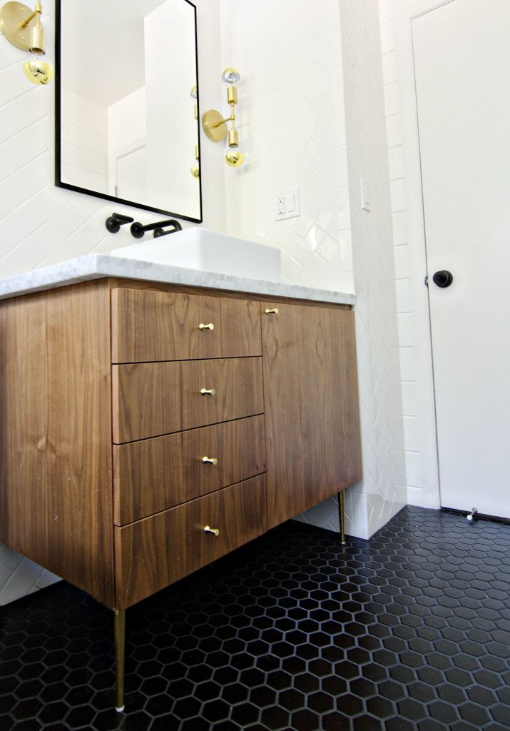 Gorgeous serene bathroom. LOVE the mid-century vanity with brass knobs, matte black hex floor ties, matte black wall mount faucet, brass wall sconces, and black framed mirror.